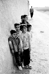 Children wait in line to go to work to the field of potatoes. Desert zones close to Isfahan- Iran 2013
